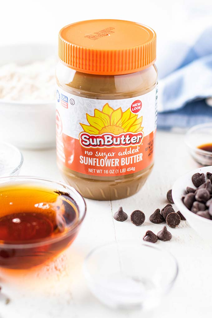 A jar of SunButter sitting with the ingredients for these healthier christmas cookies.