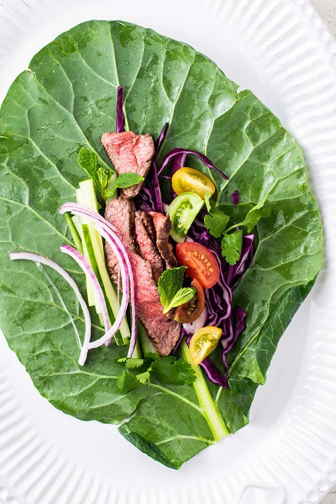 A collard green prepared and filled with steak salad ingredients.