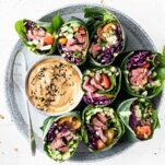 A plate with thai steak salad wraps on a plate with a creamy sunflower dipping sauce.