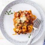 A slice of baked butternut squash casserole on a plate with a fork.