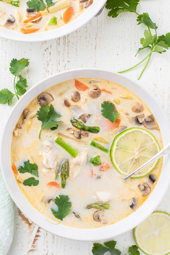 An close up look at the veggies and garnished on a bowl of tom kha gai soup recipe.