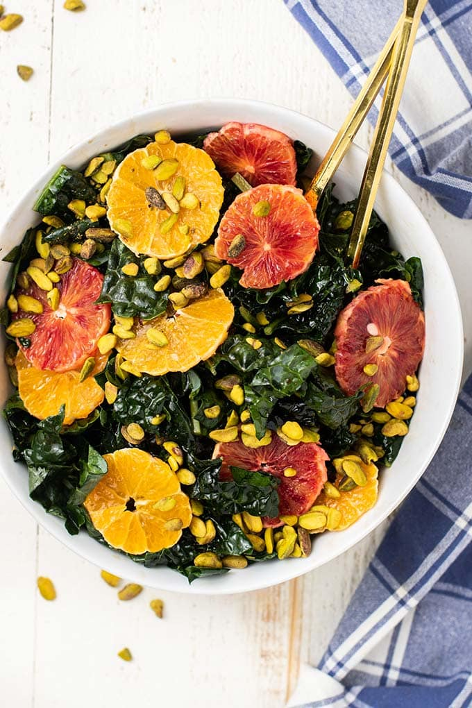 A close up look at a massaged kale salad with citrus and pistachios.