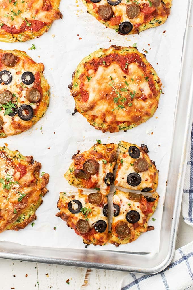 6 mini zucchini pizza crusts topped with cheese, sausage, and olives.