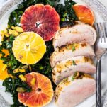 A plate shown with a kale and blood orange salad served with slices of a baked pork tenderloin.