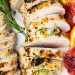A close up of a marinated baked pork tenderloin sliced on a platter.