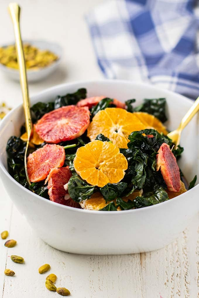 Massaged kale in a bowl being topped with blood orange and tangerine slices.
