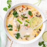 A close up look at a bowl of tom kha gai with lots of vegetables.