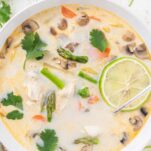 A close up look at a bowl of Tom Kha Gai garnished with lime and cilantro.