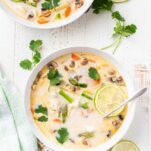 Two bowls of tom kha gai with lime.