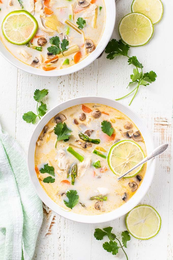 Two bowls of paleo coconut milk soup with chicken and asparagus.