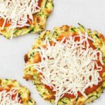 Mini zucchini pizza crusts on a baking tray topped with pizza sauce and mozzarella cheese.