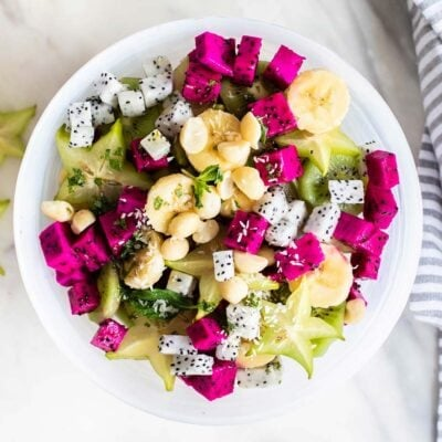 A top down view of a white bowl filled with dragon fruit, star fruit, and bananas.