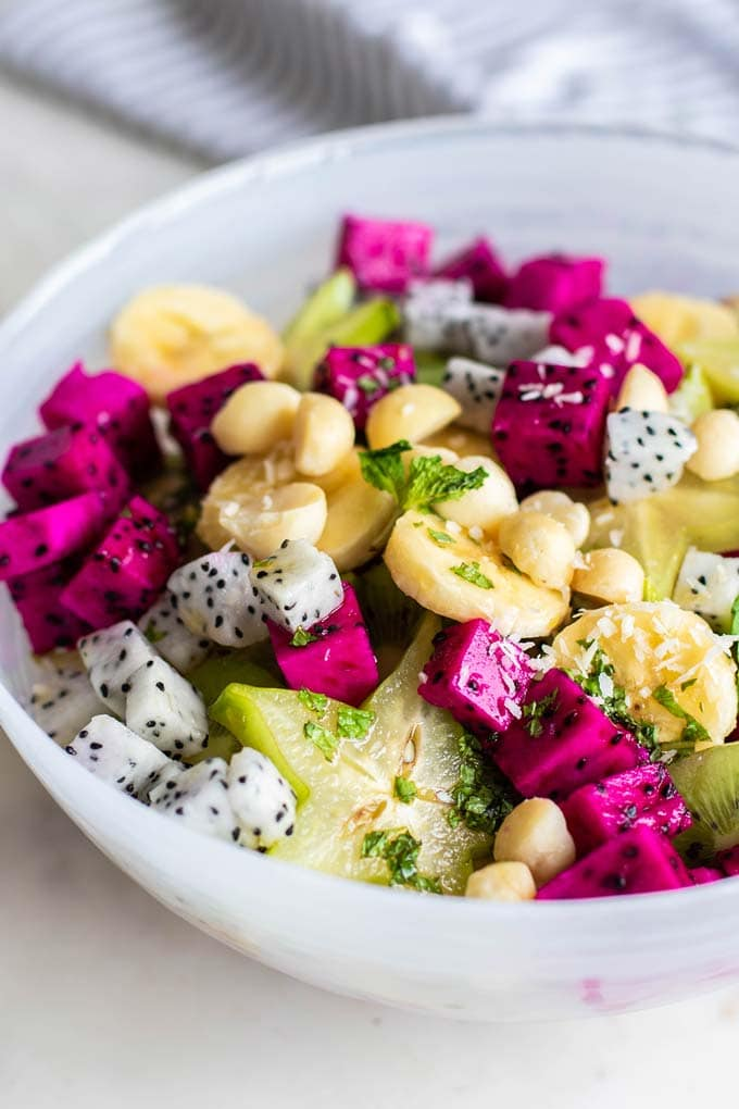 A close up side view of a dragon fruit salad topped with macadamia nuts.