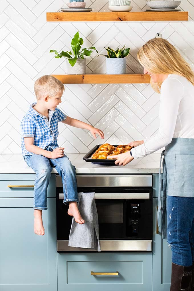 Michelle taking hot pretzels out of the oven and showing Xander.