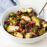 A bowl filled with crispy roasted brussels sprouts and big chunks of crisp bacon.