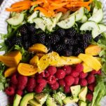 A platter with rows of berries, avocado, beets, and peppers.