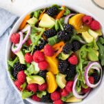 A large salad bowl filled with arugula, beets, and berries.