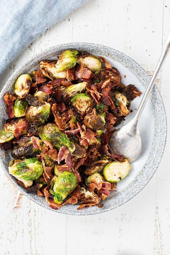 A top down view of crispy roasted brussels sprouts with big chunks of crisp bacon.