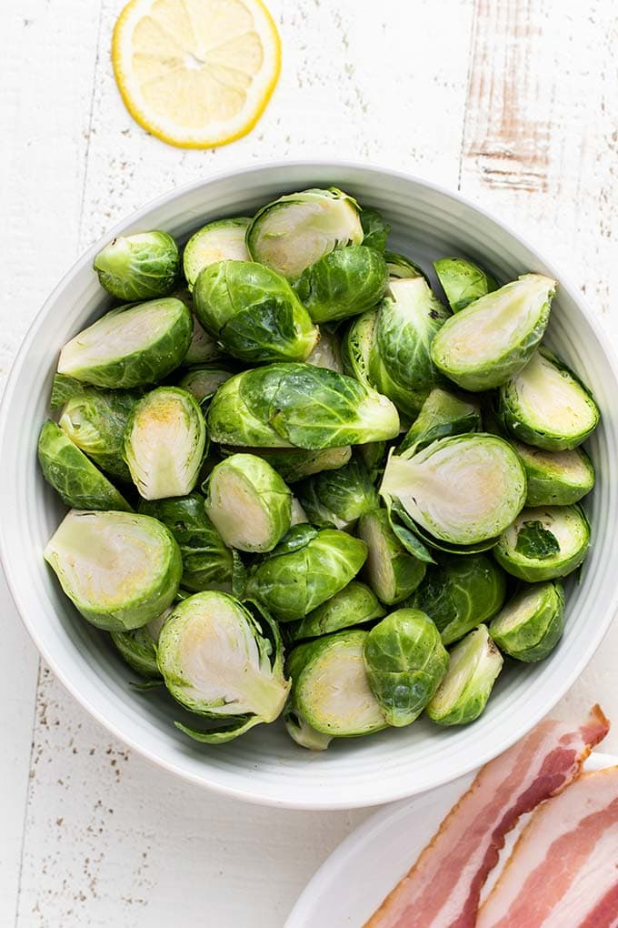 A bowl of vibrant green brussels sprouts, showing how to trim and halve them for this recipe.