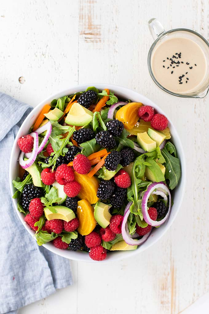 A salad bowl filled with arugula, avocado, berries, onions, and peppers.