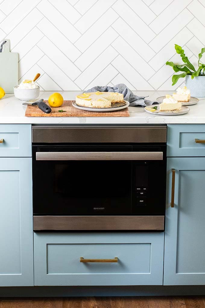 A cheesecake, some lemons, and a bowl of whipped cream sitting on a counter next to the Sharp Superheated Steam Oven.
