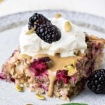 A slice of baked oatmeal served with extra blackberries.