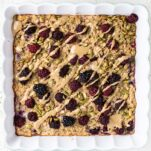 A top down view of blackberry baked oatmeal drizzled with sunflower seed butter.