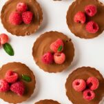 A top down view of a platter of mini cheesecakes garnished with raspberries and mint.