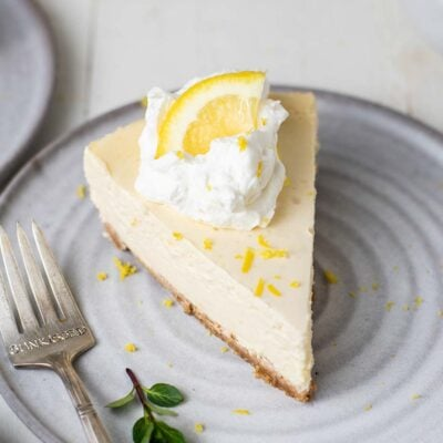 A slice of Greek yogurt lemon cheesecake garnished with whipped cream and lemon zest.
