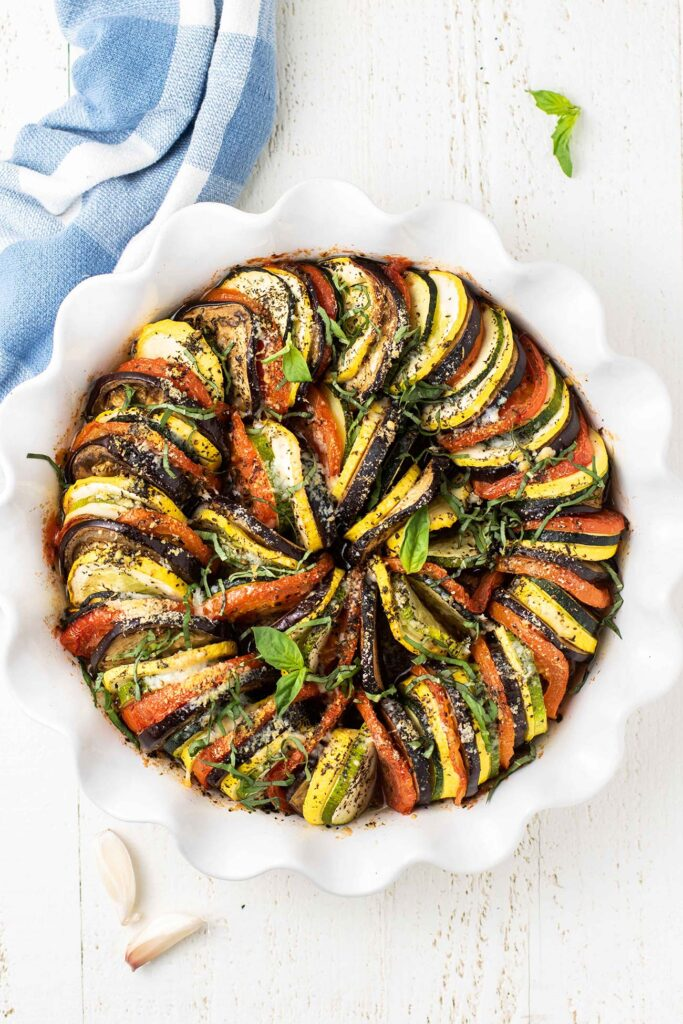A baked ratatouille topped with parmesan and basil.