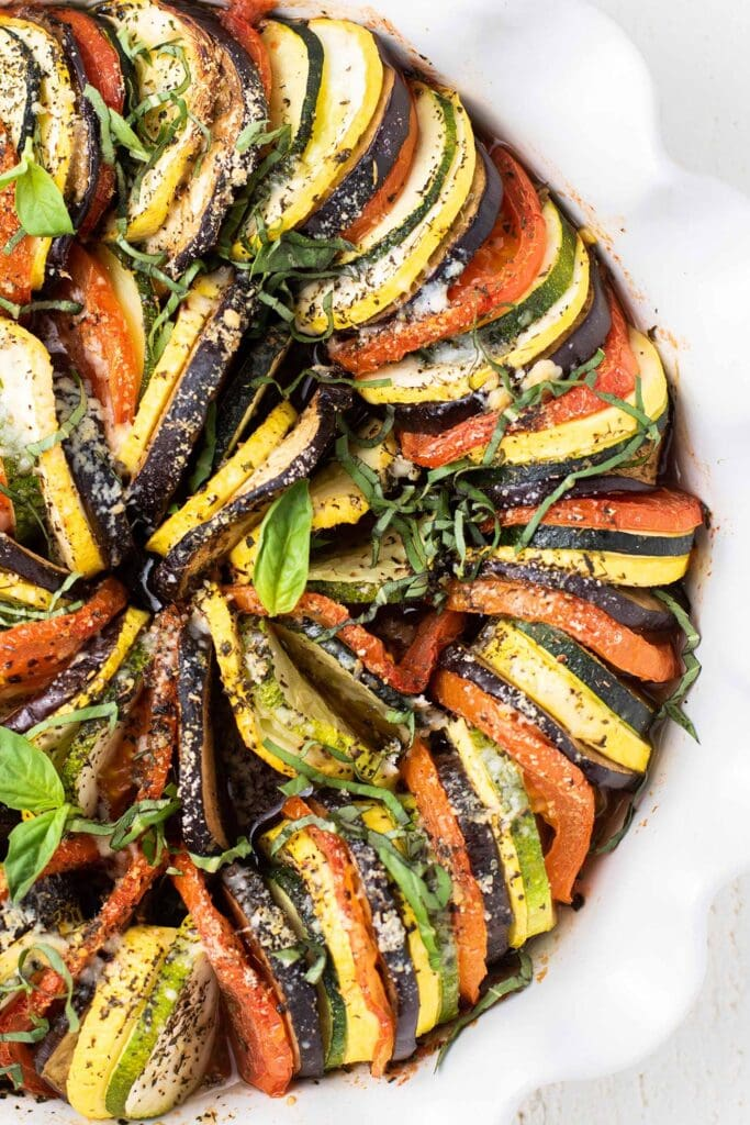 A close up look at a baked ratatouille topped with parmesan and basil.
