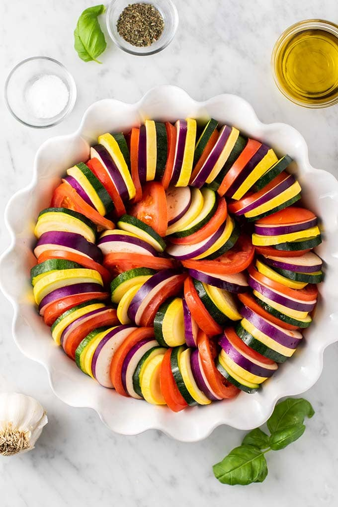 A baking dish shown with layers of tomatoes, eggplant, zucchini, and summer squash.
