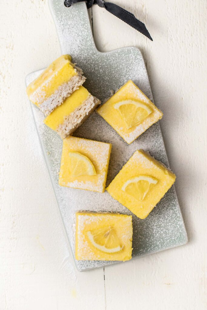 A blue board with lemon bars garnished with lemon wedges.