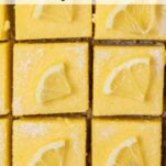 A close up look at 6 lemon bars garnished with lemon wedges.