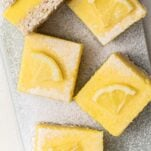 A close up look at lemon bars cut into squares.