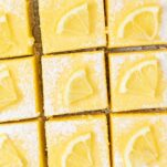 A close up of lemon bars cut into squares.
