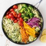 A skillet with zoodles tossed in a creamy lemon sauce topped with colorful veggies.