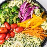 A close up of a skillet filled with zoodles primavera.