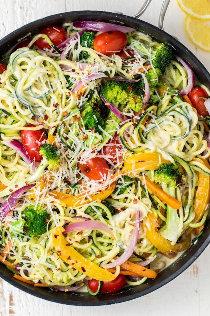 A close up of zoodles primavera shown with the veggies tossed into the mixture.