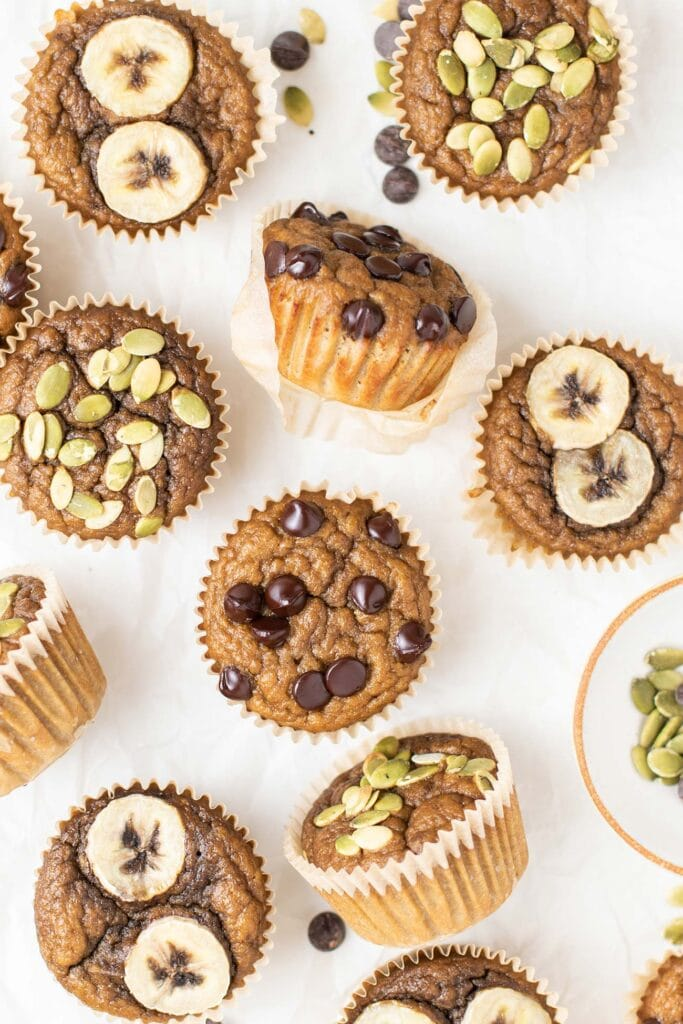 A bunch of muffins shown laid out and topped with different things.