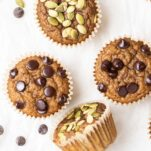 Muffins and bananas shown with chocolate chips on a white table.