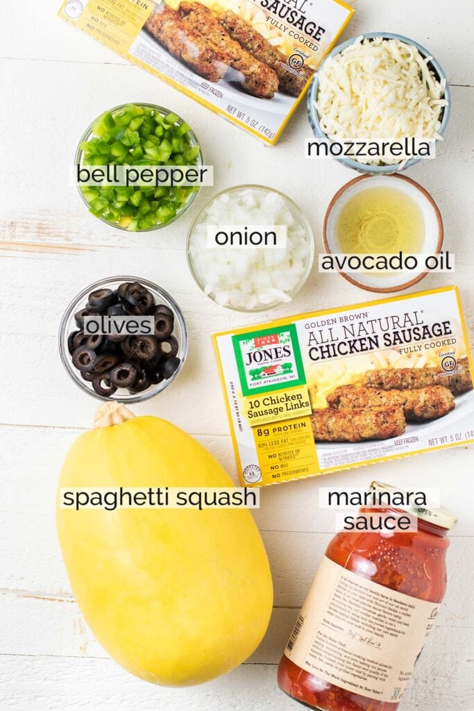 The ingredients needed to make sausage stuffed spaghetti squash shown prepared with labels.