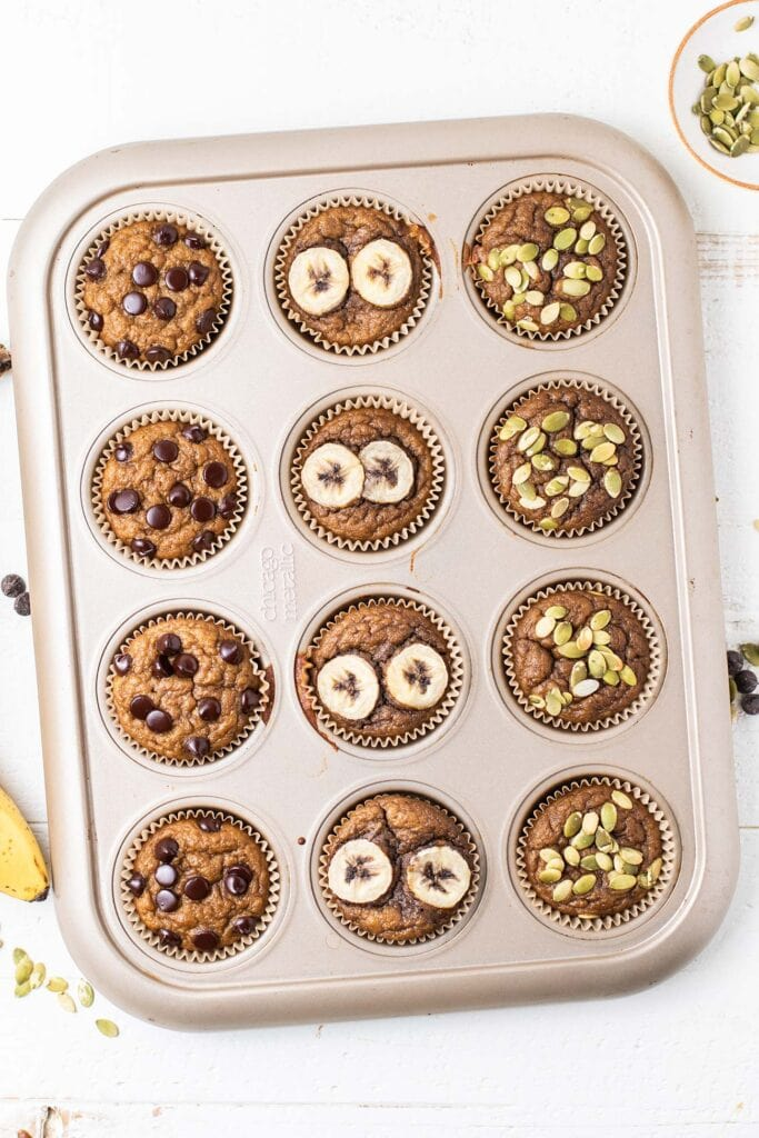 A 12 muffin tin shown with baked gluten free banana muffins.