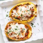 Two squash halves shown stuffed and baked with a layer of cheese on top.