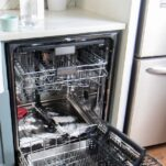 A dishwasher open, showing baking soda sprinkled along the bottom.