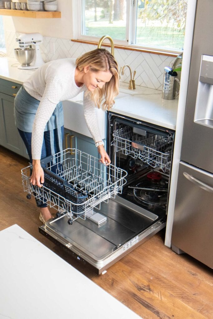 Michelle taking the bottom rack out of the dishwasher.