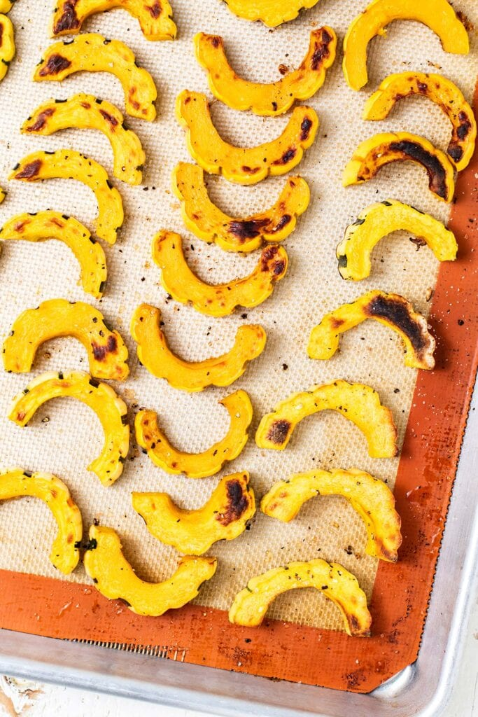 A baking sheet with roasted delicata squash.
