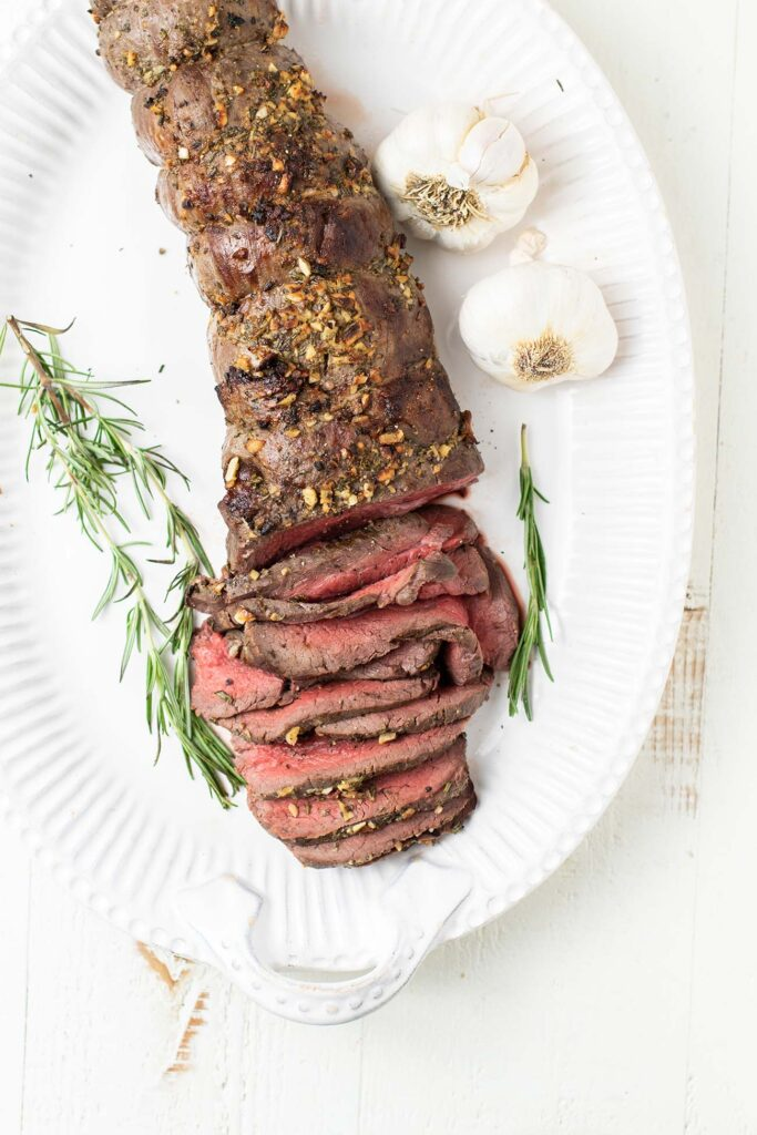A beef tenderloin roast on a white platter garnished with rosemary.