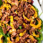 A close up look at a spinach salad with bacon dressing.