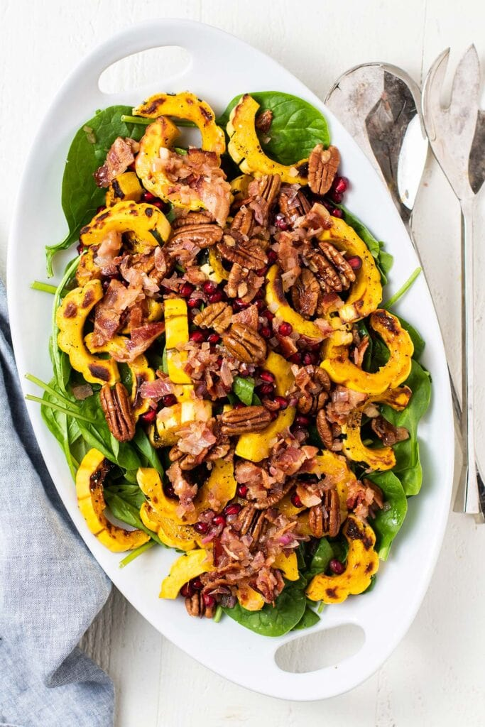 A white platter with a delicata squash spinach salad with bacon dressing.